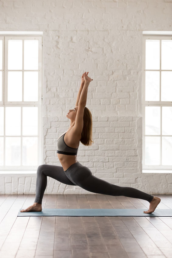 Sporty woman in grey sportswear, bra and leggings practicing yoga, standing in anjaneyasana pose, attractive girl doing Horse rider exercise, working out at home or in yoga studio vertical photo