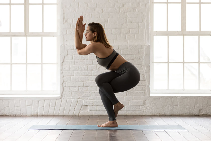 Beautiful woman wearing grey sportswear, pants and bra standing in Eagle pose, Garudasana exercise, attractive girl practicing yoga, working out at home or in modern yoga studio, side view