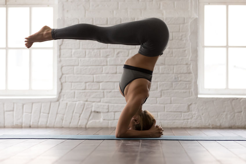 Attractive young woman practicing yoga, standing in headstand pose, variation of salamba sirsasana exercise, beautiful girl in grey sportswear, leggings and bra working out at home or in yoga studio