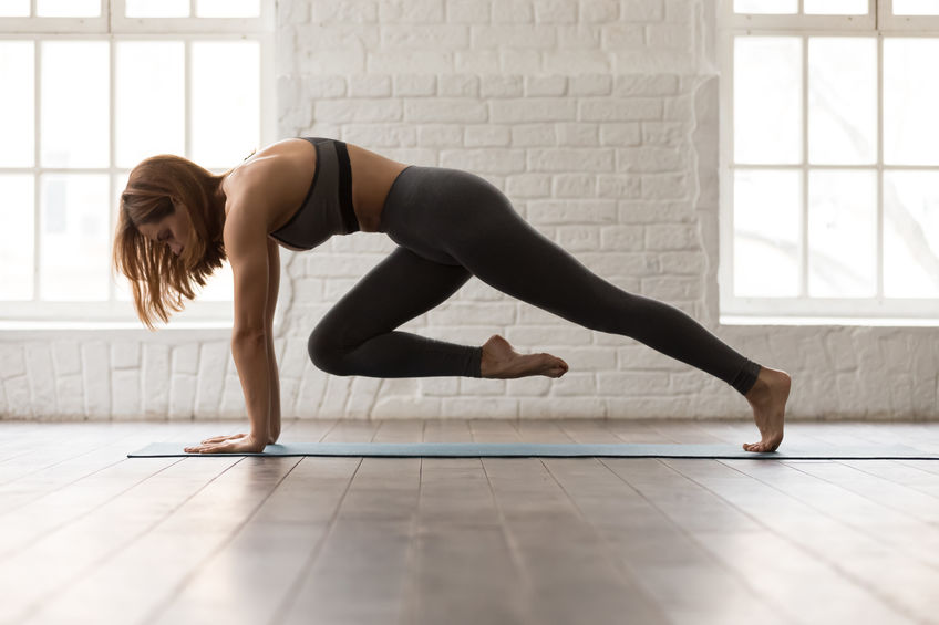 Attractive woman in grey bra and leggings practicing yoga, doing Knee to Forehead exercise, phalankasana, variation of Plank pose with lifted leg, girl working out at home or in yoga studio