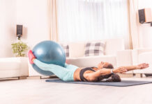 Abs and core female workout on a mat at home using fitball.