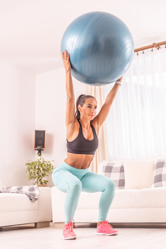 Beautiful woman squatting at home with a fit ball held above her head.