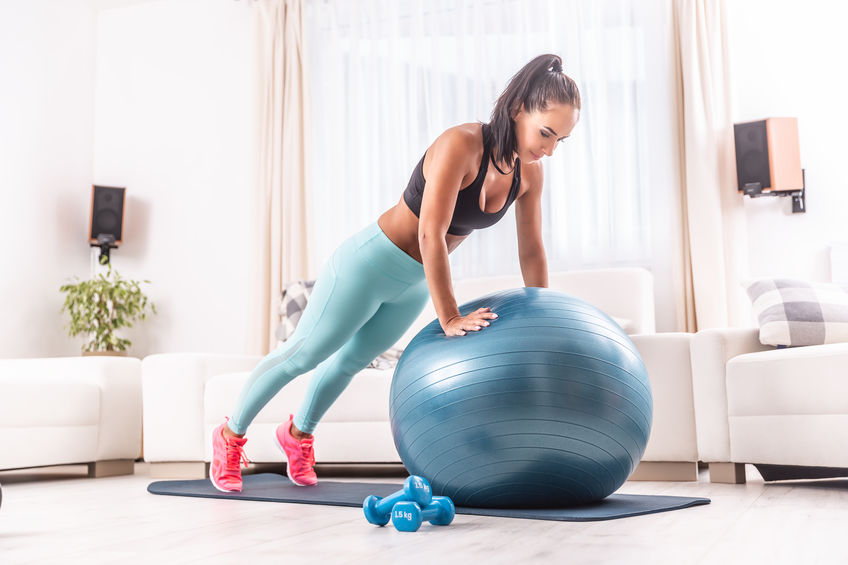 Beautiful fitness girl in leggings and crop top does a home workout on a fit ball holding plank position with her straight arms.
