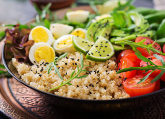 Diet menu. Healthy salad of fresh vegetables - tomatoes, avocado, arugula, egg, spinach and quinoa on a bowl