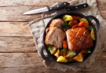 Tasty crispy pork baked in beer with vegetables and gravy close-up in a frying pan on the table. horizontal top view from above; Shutterstock ID 1223454679
