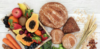 High fiber health food concept with fresh fruit, vegetables, wholegrain bread, nuts and cereals. Foods high in antioxidants, anthocyanins, omega 3 fatty acids and vitamins. Rustic background, top view.
