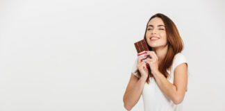 Portrait of a happy young woman holding chocolate bar isolated over white background