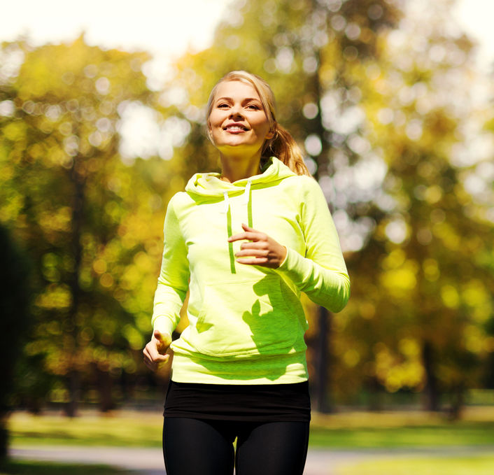 fitness and lifestyle concept - female runner jogging outdoors