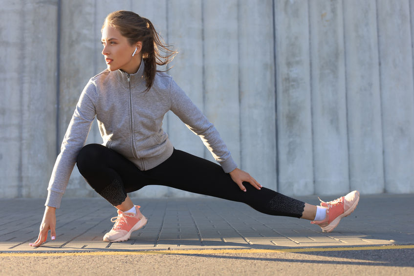 Young attractive sporty girl warming up outdoors, doing stretching at sunset or sunrise in city.