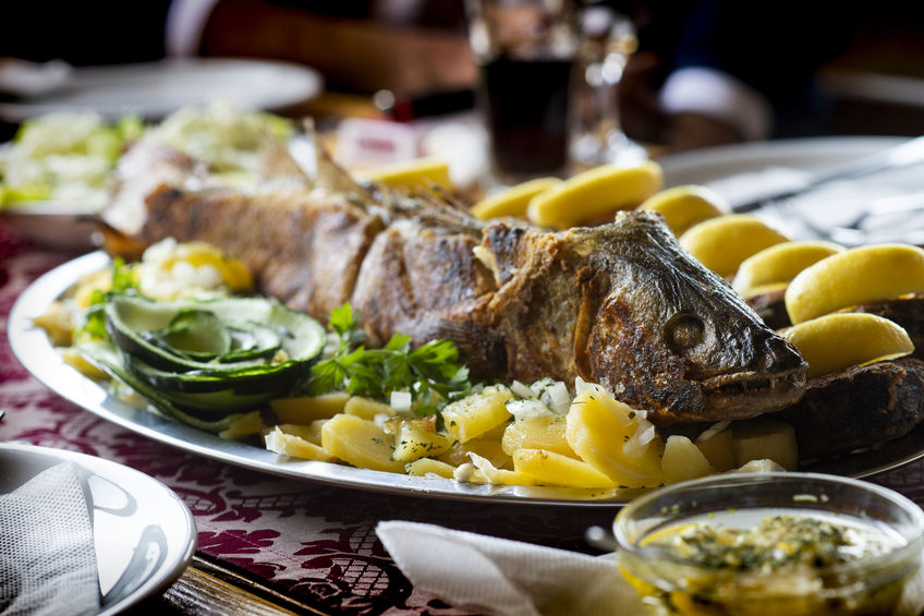 Perch fish grill dish baked whole grilled on a plate with vegetables and lemon on top for the menu isolated