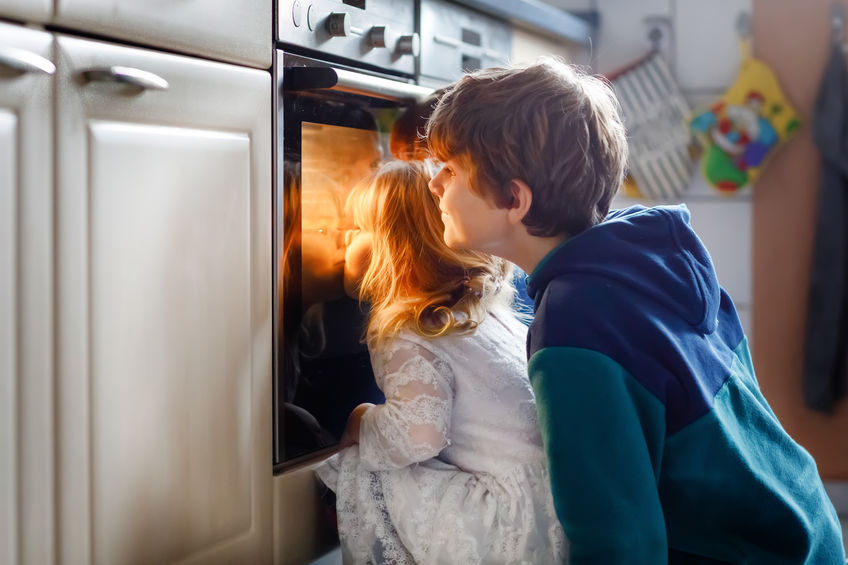 Little toddler girl and two kids boys baking, pizza or cookies in kitchen. Three children, siblings, brothers and sister sitting near oven and waiting. On thanksgiving or christmas holiday