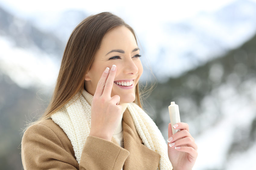 Happy lady applying facial moisturizer cream in winter