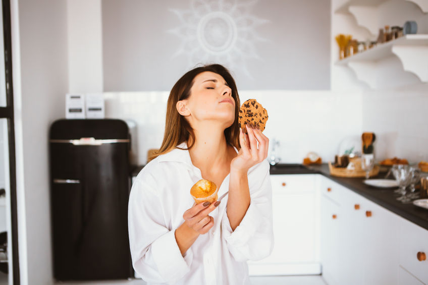 Young girl in white shirt stand on the kitchen and eat cakes.