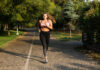 Young attractive plus size woman in pink sporty top and leggings thoughtfully looking in camera running in city park