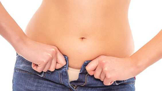 Fat woman in blue jeans on a white background.