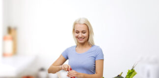 healthy eating, vegetarian food, dieting and people concept - smiling young woman cooking vegetable salad over kitchen background