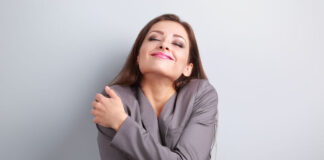 Happy business woman hugging herself with natural emotional enjoying face. Love concept of yourself